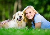 stock photo of dog park  - Woman with dog lying on the green grass in the park - JPG