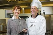 Mature head cook posing with the female manager in a professional kitchen