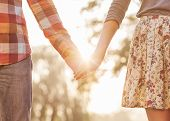 stock photo of romantic love  - Young couple in love walking in the autumn park holding hands looking in the sunset - JPG