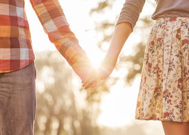 picture of jeans skirt  - Young couple in love walking in the autumn park holding hands looking in the sunset - JPG