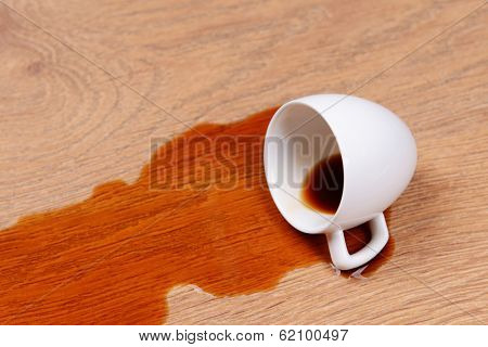 Overturned cup of coffee on floor close-up