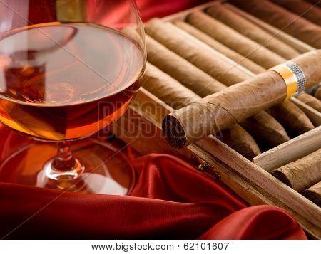 cuban cigar and  liquor  over red satin