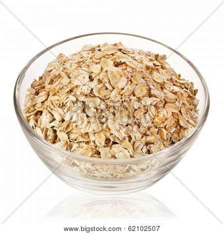 oat flake in glass bowl close up isolated on white background