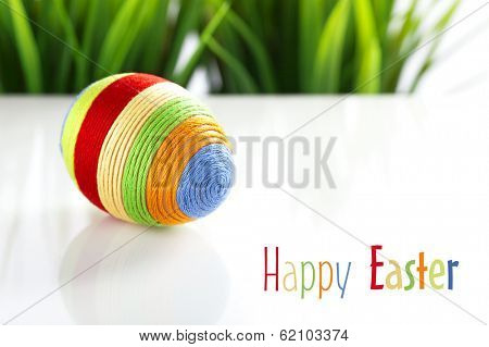 Easter greetings card. Egg with colorful yarn on white. Some grass in background. Space for text