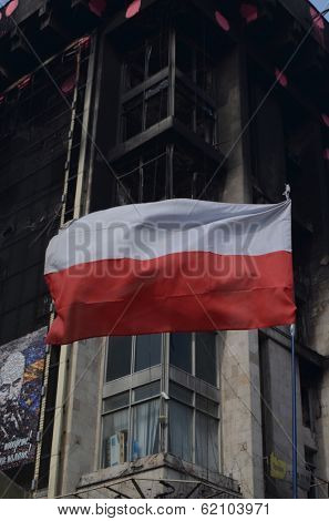 KIEV, UKRAINE -MAR 24, 2014: Downtown of Kiev.Polish flag.Burnt down the House of trade unions as a background. Riot in Kiev and Western Ukraine.March 24, 2014 Kiev, Ukraine