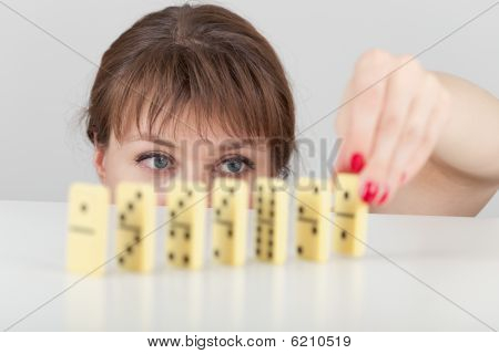 Girl Builds Line Of Dominoes Counters Close Up