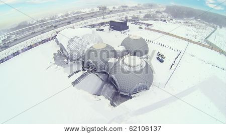 Semicircular hangar for helicopters on cloudy winter day. Aerial view