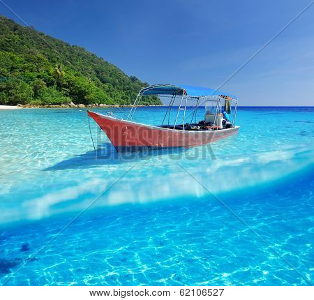 Beautiful beach and motor boat with white sand bottom underwater and above water split view