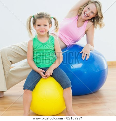 Smiling pregnant woman exercising on exercise ball with young daughter in a fitness studio