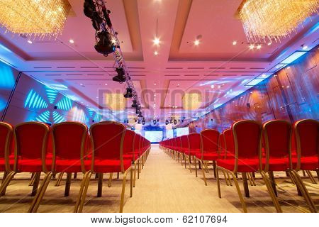Meeting room with red chairs and colored illumination