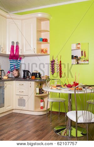 Little girl upside down sitting on the shelves in the kitchen with table and dishes