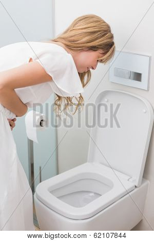 Young woman with stomach sickness about to vomit into a toilet