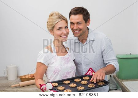 Portrait of happy young couple preparing cookies together in the kitchen at home