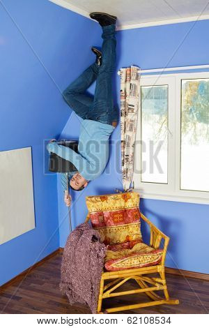 Man in jeans standing on the ceiling holding a lamp