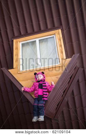 Little girl sitting on the brown roof of the upside-down house