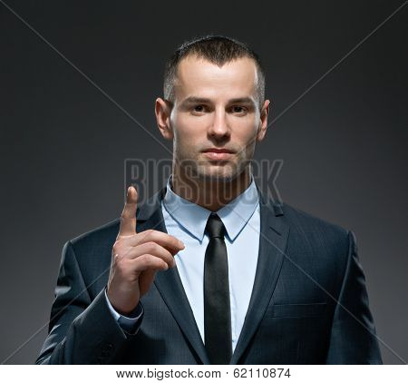 Portrait of making attention gesture business man wears business suit and black tie