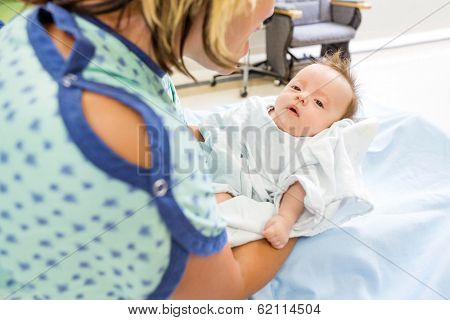 Mid adult woman playing with cute newborn babygirl in hospital room