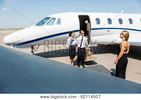Elegant woman walking towards private jet while pilot and stewardess standing at airport terminal