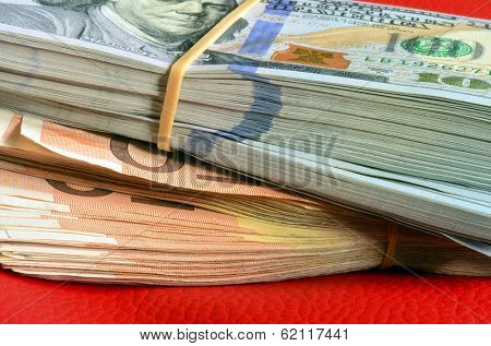 Stacks of ten thousand american dollars and five thousand euro on red leather background.