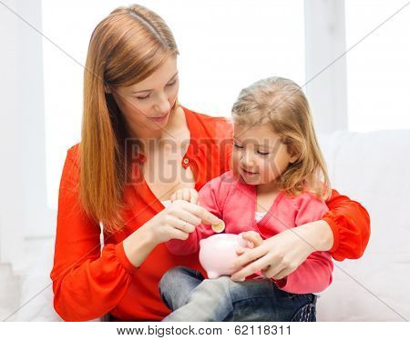 family, children, money, investment and happy people concept - happy mother and daughter with small pink piggy bank