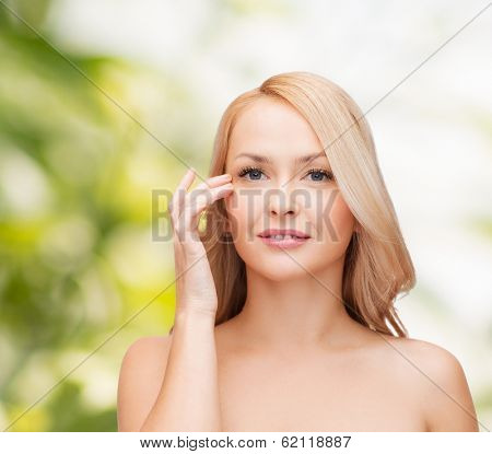 heath and beauty concept - face of beautiful woman touching her eye area