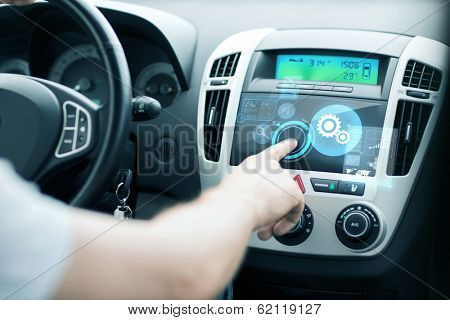 transportation and vehicle concept - man using car control panel