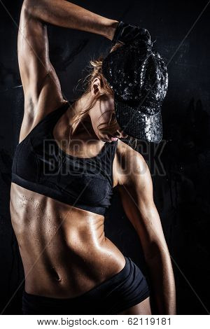 Sexy woman in a cap posing on dark background