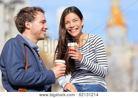 Happy couple drinking coffee talking flirting having fun together. Happy urban young man and woman laughing relaxing outside with disposable coffee cup. Caucasian Asian Interracial couple.