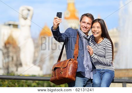 Happy urban city couple on travel in Barcelona taking selfie self portrait photograph with smart phone camera. Happy young man and woman on Placa de Catalunya, Catalonia Square, Barcelona, Spain.