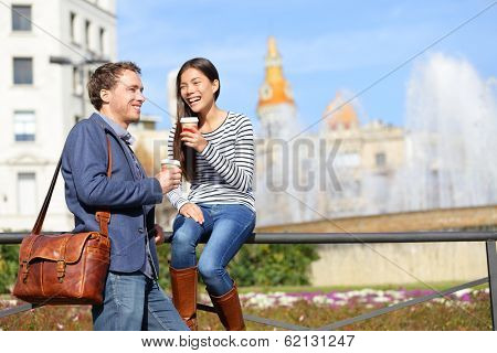 Happy couple drinking coffee talking in Barcelona flirting having fun on travel. Happy urban young man and woman laughing relaxing on Placa de Catalunya, Catalonia Square, Barcelona, Spain.