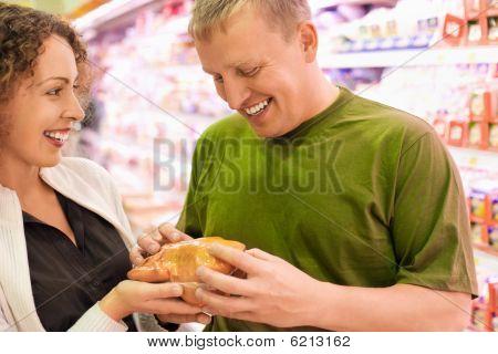 Mujer y joven sonriente compran pollo en el supermercado