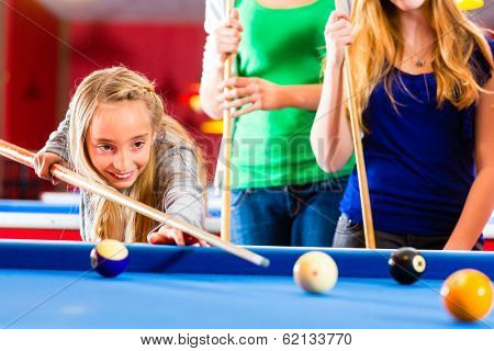 Family playing together billiard. Brother kick off with queue and balls on pool table