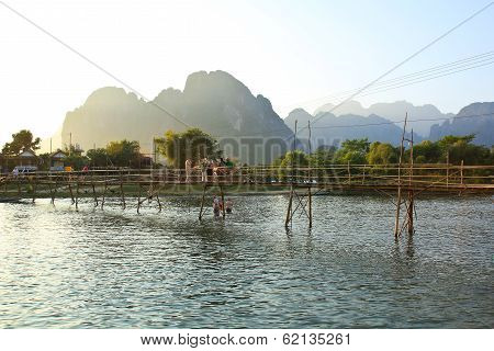 Vang Vieng, Laos - Feb 1: Local People And Tourists Cross The Bamboo Bridge At Sunset