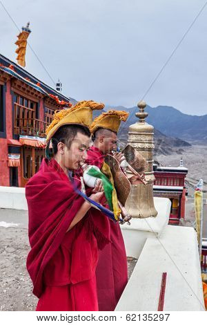 THIKSEY, INDIA - SEPTEMBER 4, 2011: Two Tibetan Buddhist monks blowing conches during morning pooja, Thiksey gompa, Ladakh, India