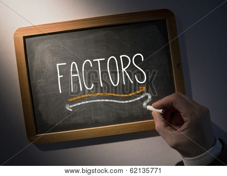 Hand writing the word factors on black chalkboard
