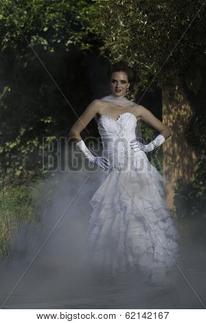 Beautiful bride posing in courtyard fountain with mist