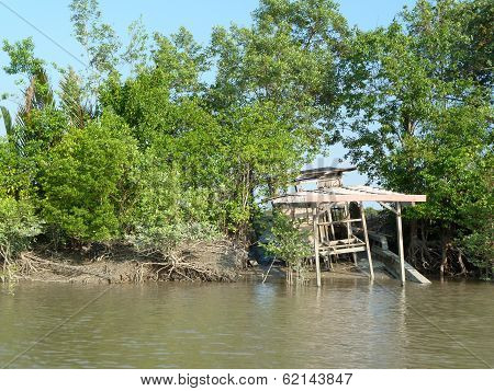 Abandoned boat on Sungai Santubong riverbank