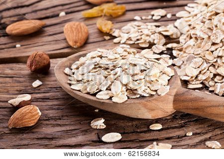 Rolled oats in the wooden spoon over old wooden table.