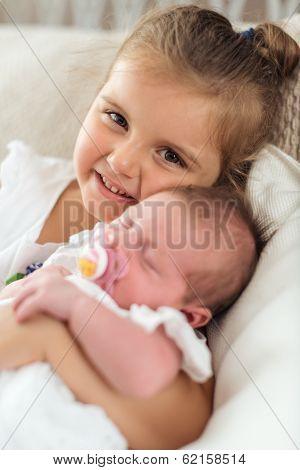 girl holding her newborn sibbling