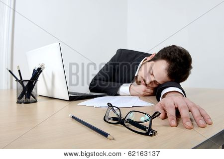 Young businessman sleeping on the office desk