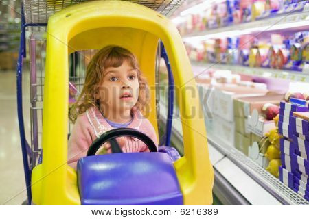 Little Girl Goes For Drive On Shoppingcarts In Supermarket