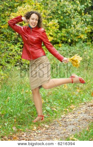Young Woman With Leaves In Hands In Wood In Autumn