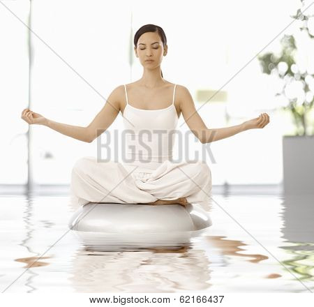 Young woman sitting in yoga position, relaxing eyes closed.