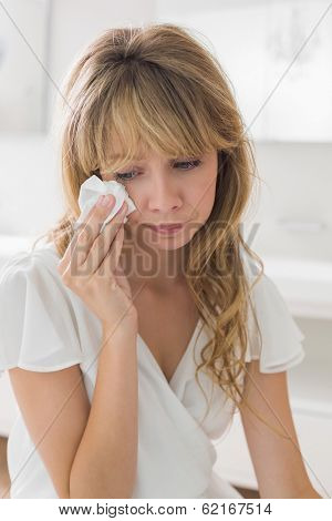 Sad young woman crying in the bathroom at home