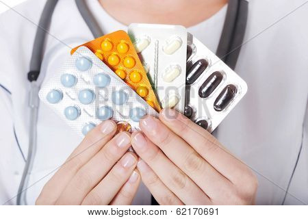 Young female doctor with pills. Isolated on white.