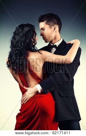 Beautiful young couple in love dancing passionate dance. Studio shot.