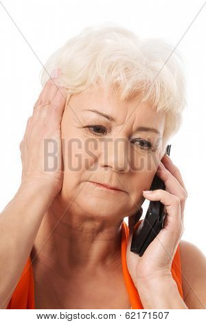 An old lady talking through phone.She is receiving bad news. Isolated on white.