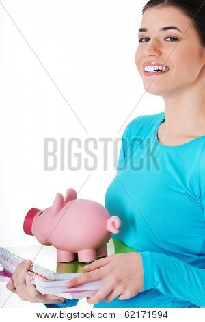 Casual student woman holding workbook and piggy-bank. Isolated on white.