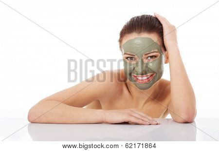 Beautifu toplessl woman with facial mask with hands on table. Isolated on white.