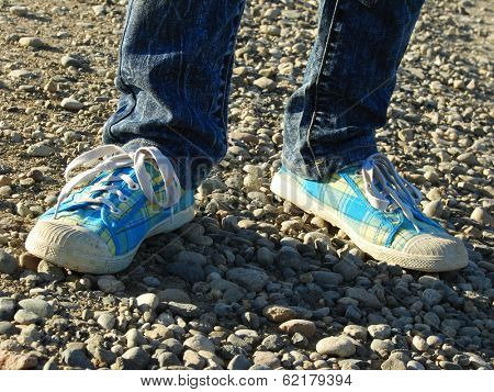 kid legs with gym shoes on stone track.